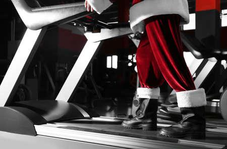 Authentic Santa Claus training on treadmill in modern gym, closeup Reklamní fotografie