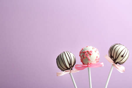 Tasty cake pops with bows on violet background. Space for text