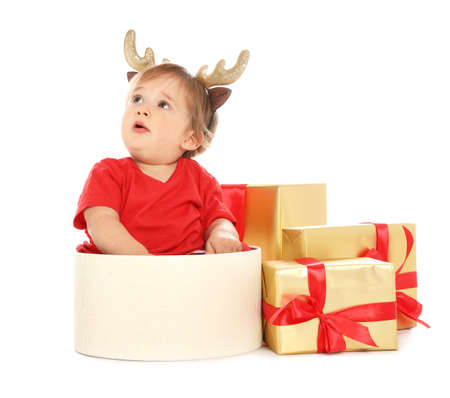 Festively dressed baby with Christmas gifts on white background Stok Fotoğraf