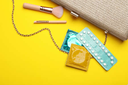 Flat lay composition with birth control pills and condoms on yellow background. Safe sex concept