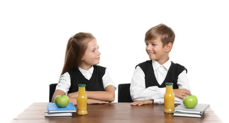 Happy children with healthy food for school lunch at desk on white background