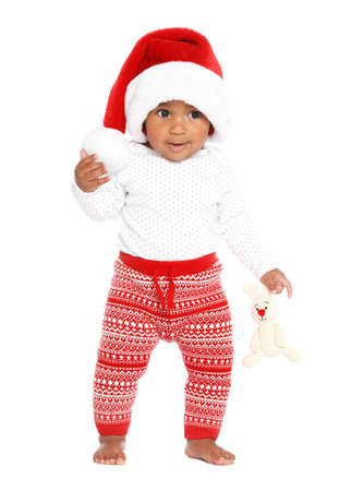 Festively dressed African-American baby with toy on white background. First Christmas