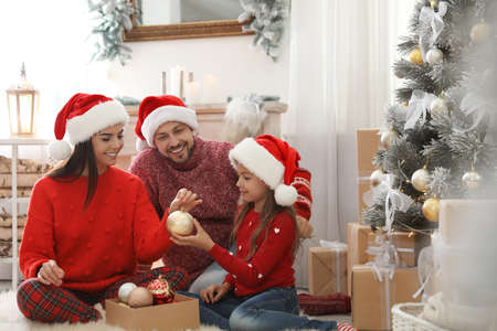 Happy family decorating Christmas tree at home Imagens