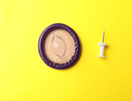 Purple condom and pin on yellow background, flat lay Banco de Imagens