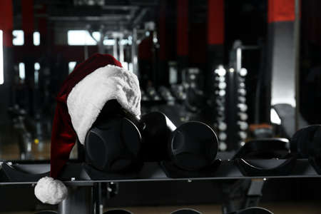 Santa hat on stand with dumbbells in modern gym