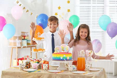 Niños felices en la fiesta de cumpleaños en la habitación decorada Foto de archivo