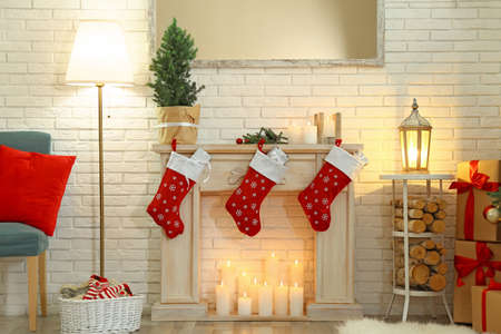 Beautiful Christmas interior with decorative fireplace and red stockings