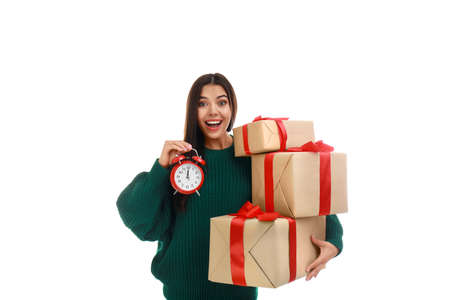 Happy young woman with Christmas gifts and alarm clock on white background
