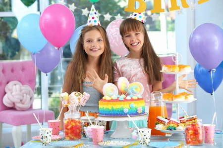 Happy children at birthday party in decorated room Banco de Imagens