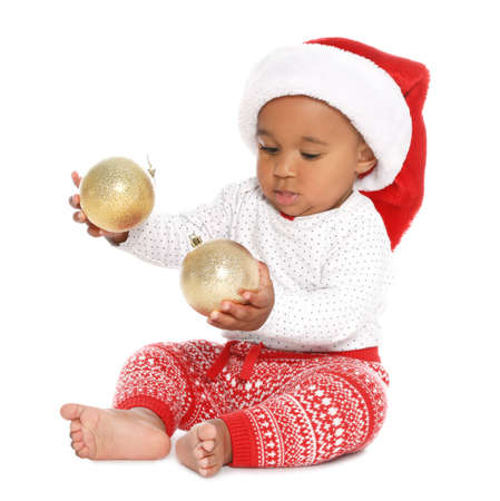Festively dressed African-American baby with Christmas decorations on white background