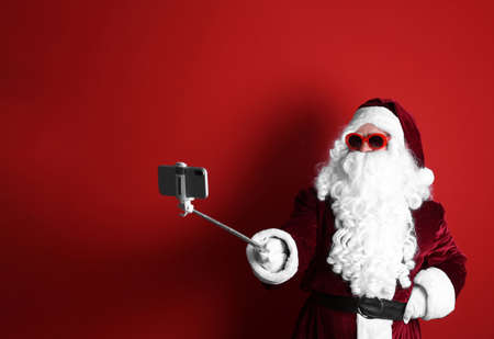 Authentic Santa Claus taking selfie on red background Stok Fotoğraf