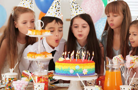 Happy children blowing out candles on cake at birthday party indoors Imagens