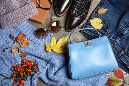 Flat lay composition with warm clothes and autumn leaves on wooden background Stock Photo