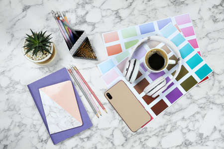 Flat lay composition with phone, notebook and color palettes on white marble table. Designers workplace Stock Photo