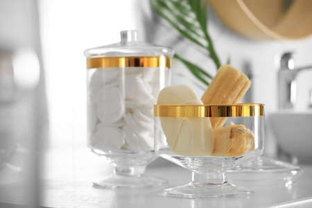 Jars with cotton pads and loofah sponges on countertop in bathroom