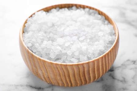 Bowl with white sea salt on marble table, closeup. Spa treatment Zdjęcie Seryjne