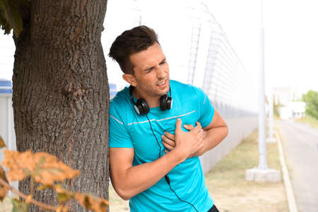 Young man having heart attack while running outdoors Banque d'images