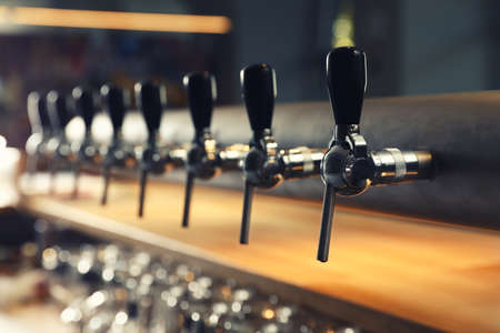 Row of shiny beer taps in pub