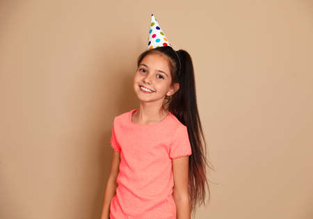 Happy girl with party hat on brown background. Birthday celebration