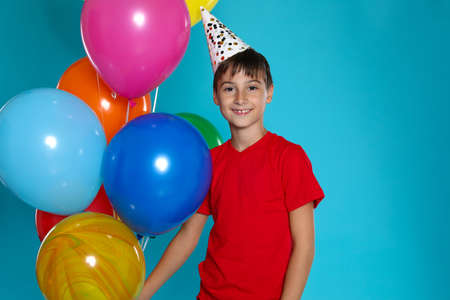 Happy boy with balloons on blue background. Birthday celebration Imagens