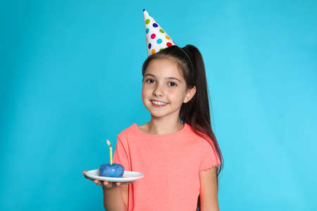 Happy girl holding birthday sweetness with candle on blue background