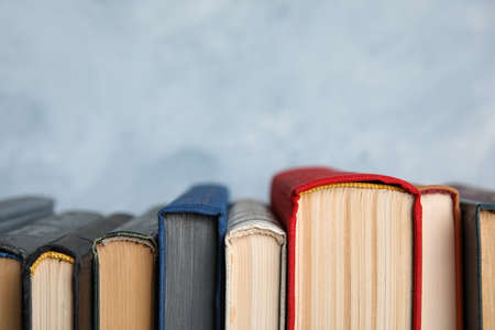 Stack of hardcover books on light blue background, closeup. Space for text