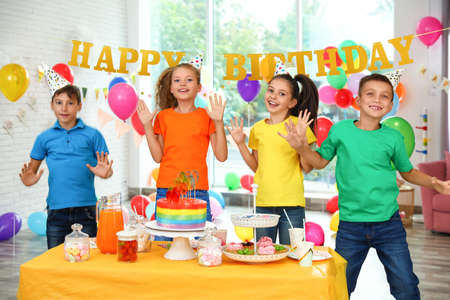 Happy children at birthday party in decorated room