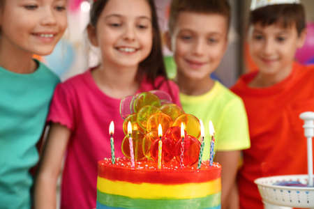 Children near cake with candles at birthday party indoors, closeup