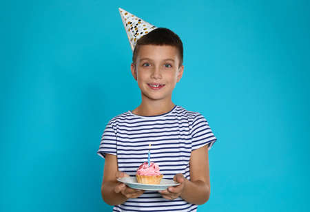 Happy boy holding birthday cupcake with candle on blue background Imagens