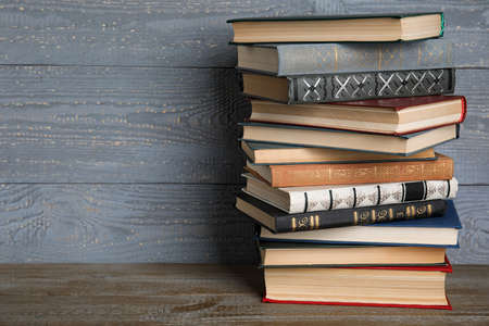 Stack of hardcover books on wooden table against grey background. Space for text