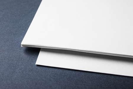 Blank paper sheets on dark grey background, closeup. Mock up for design Stockfoto