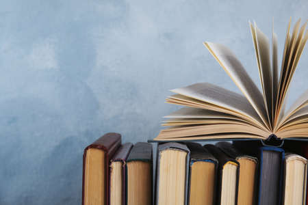 Stack of hardcover books on light blue background. Space for text