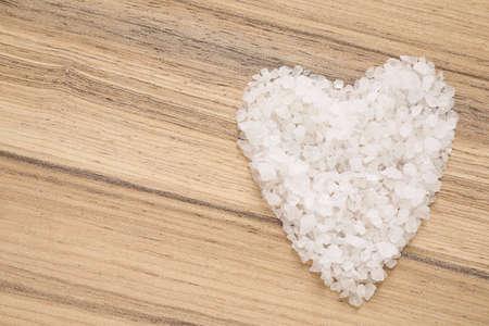 Heart shaped pile of sea salt for spa scrubbing procedure on wooden background, top view Zdjęcie Seryjne