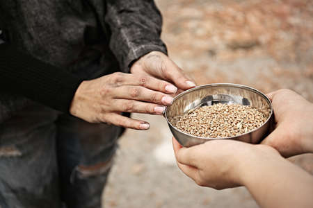 Woman giving poor homeless person bowl of wheat outdoors, closeup Stock Photo