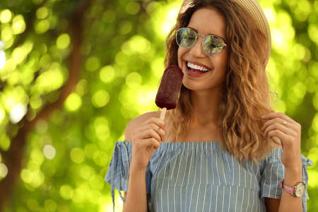 Happy young woman eating delicious ice cream outdoors. Space for text Reklamní fotografie