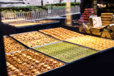 Shop with different turkish sweets, view through window glass Banco de Imagens
