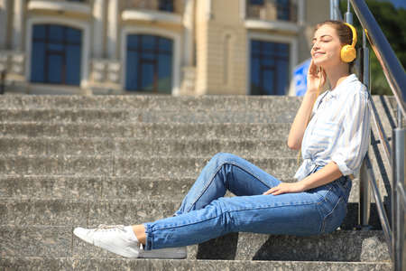 Young woman with headphones listening to music on stairs. Space for text