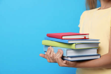 Little girl holding books on blue background, closeup. Reading concept Banque d'images - 132041223