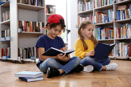 Cute little children reading books on floor in library Stockfoto