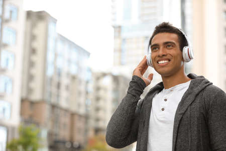 Portrait of handsome young African-American man with headphones listening to music on city street. Space for text Stock Photo