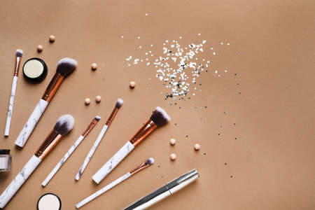 Flat lay composition with makeup brushes on brown background. Space for text