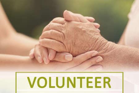 Volunteer holding hand of senior woman, closeup
