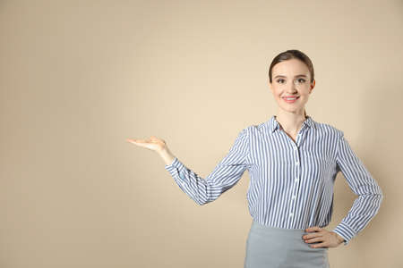Portrait of young female teacher on beige background. Space for text Reklamní fotografie