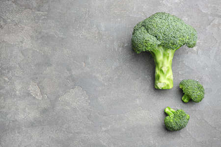 Flat lay composition of fresh green broccoli on grey stone table, space for text