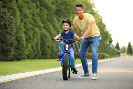 Dad teaching son to ride bicycle outdoors Reklamní fotografie - 132241468
