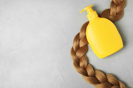 Blank bottle of cosmetic product and braided hair on light background, flat lay. Space for design