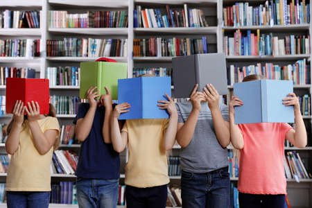 Group of little children holding books near shelves in library reading room