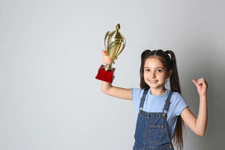 Happy girl with golden winning cup on light background. Space for text Imagens