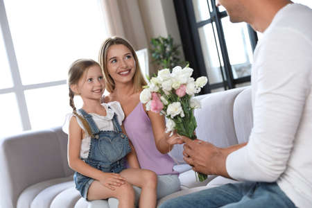 Young man congratulating his wife and daughter in living room Imagens