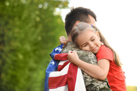 Father in military uniform with American flag hugging his little daughter at green park